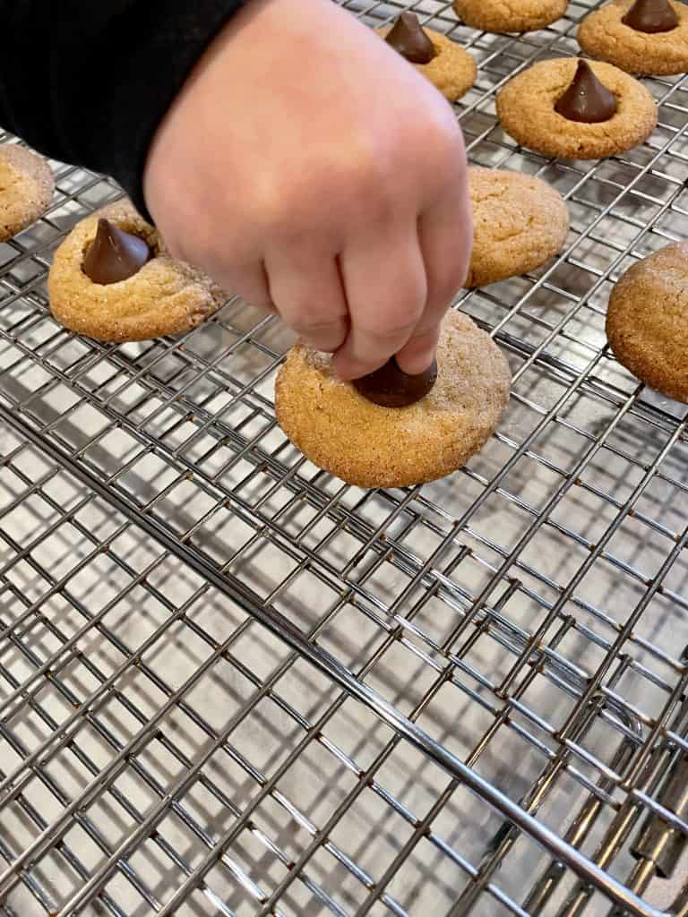 adding chocolate to peanut butter blossom cookies