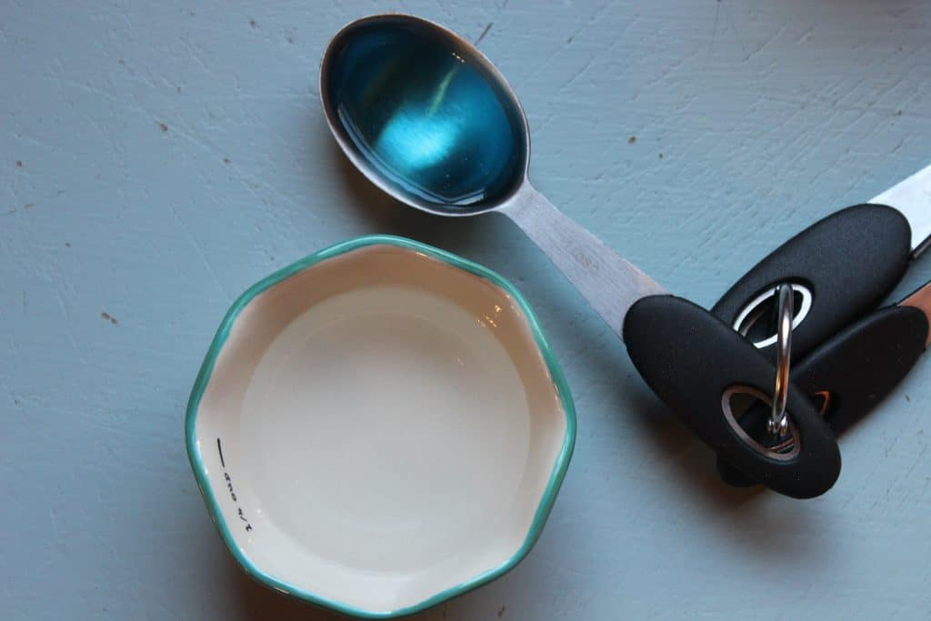 bowl of peroxide and spoon of dish soap for making a homemade stain remover