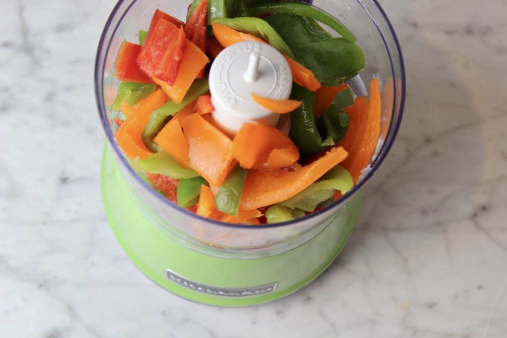 miniature food processor full of bell peppers
