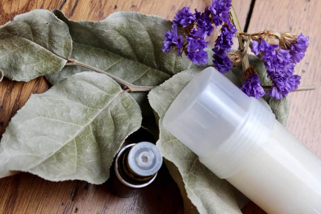 dried leaves and flowers with essential oil bottle and deodorant