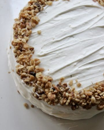 sourdough carrot cake topped with cream cheese frosting and crushed walnuts a from scratch recipe