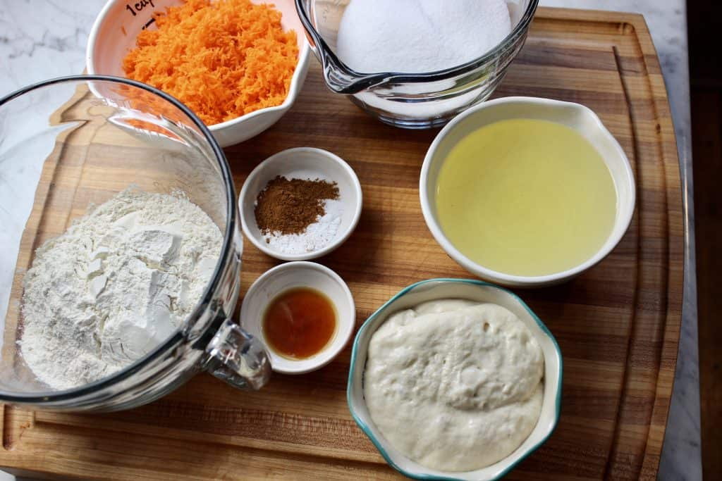 ingredients used to make sourdough carrot cake on a wooden cutting board