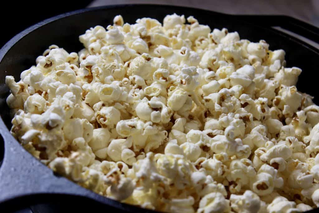 freshly popped popcorn in a cast iron pan on the stove