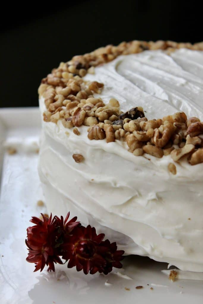 side view of sourdough carrot cake decorated with dried flowers and crushed walnuts