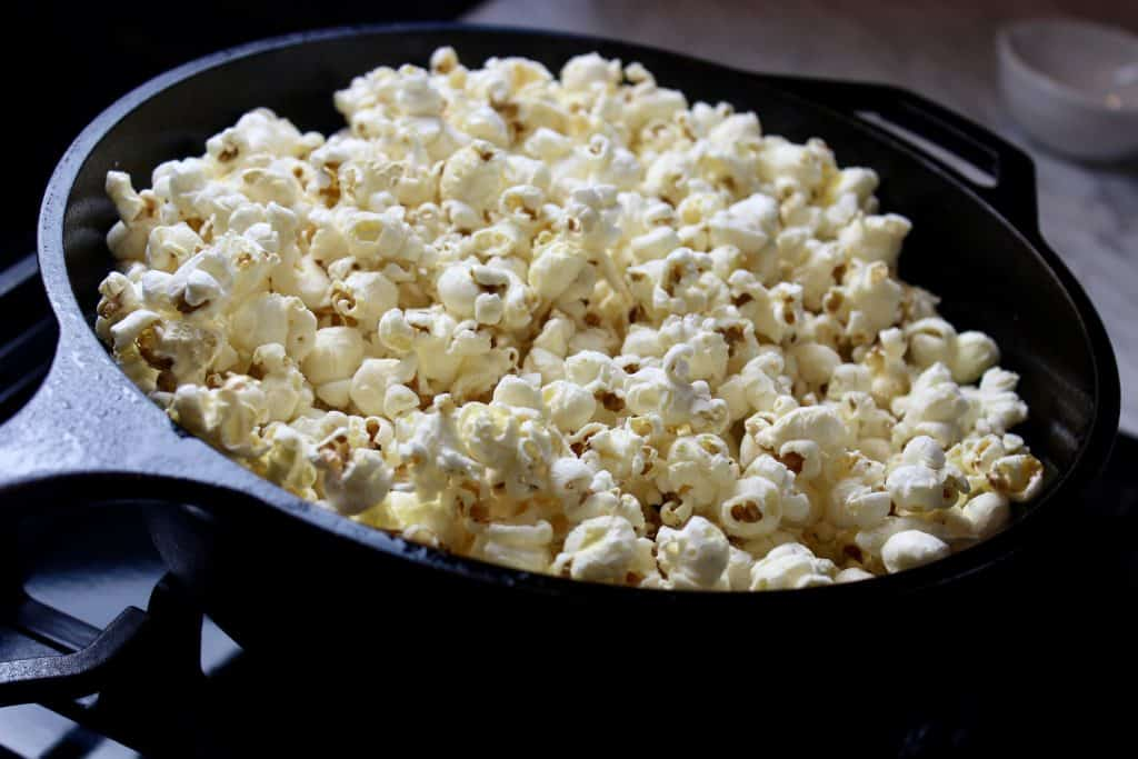 freshly popped popcorn on the stove in a cast iron pan