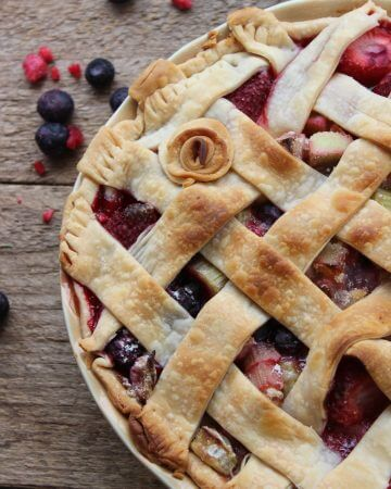 rhubarb and berry pie on a table with mixed berries