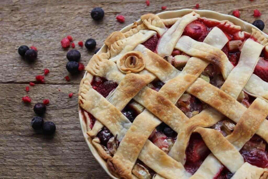 rhubarb berry pie on a wood plank with berries