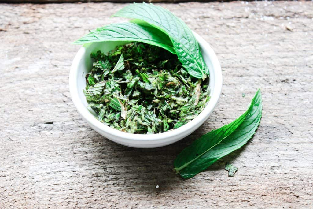 small jar of diced spearmint for use in a homemade pink himalayan salt and sugar body scrub