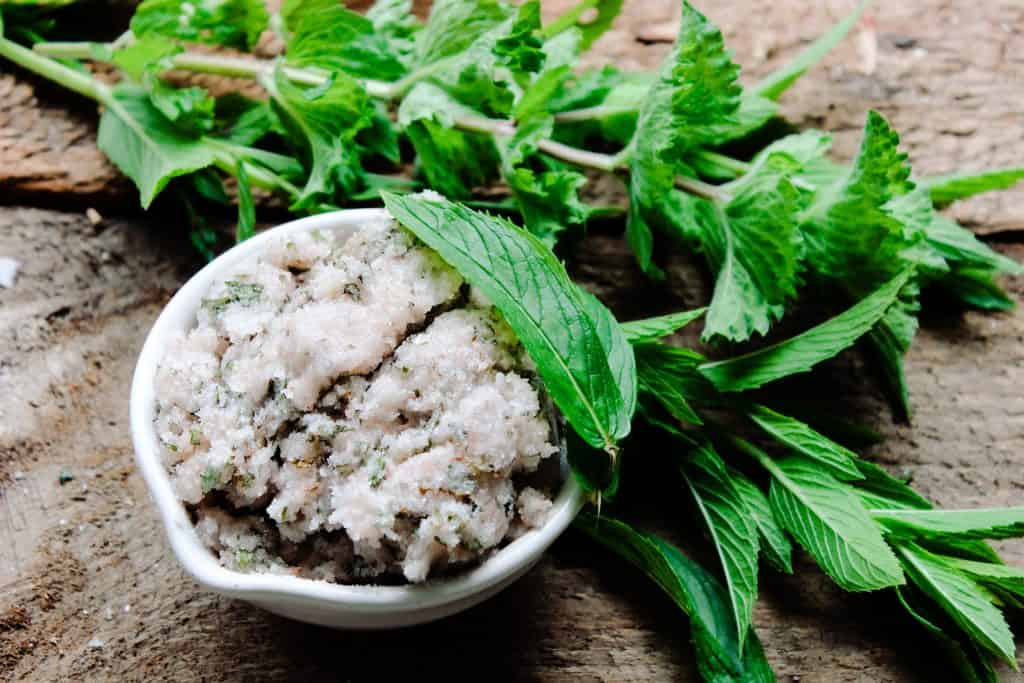 jar of pink himalayan salt and sugar body scrub with spearmint and mint leaves