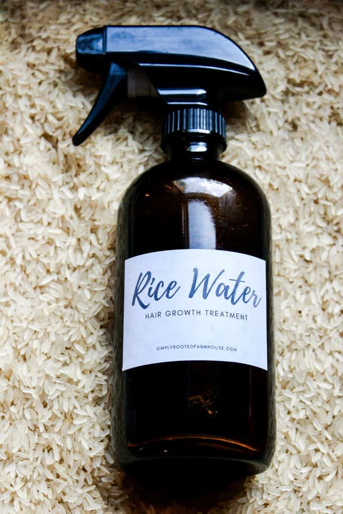 rice water hair treatment recipe in an amber glass spray bottle in a bed of rice