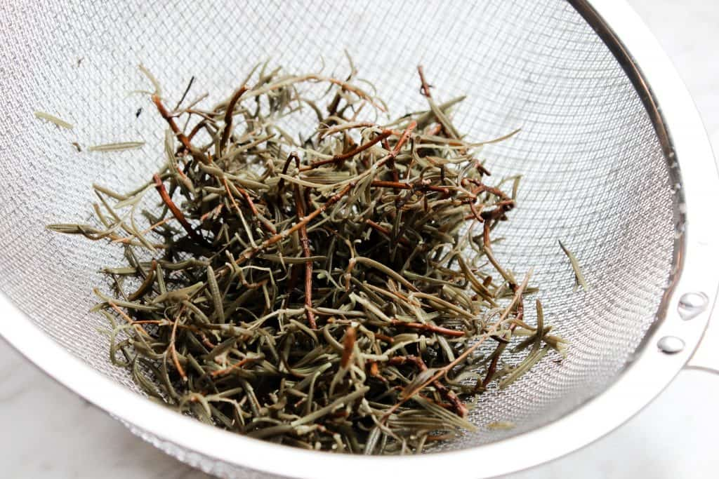 straining rosemary for a rosemary water hair growth treatment